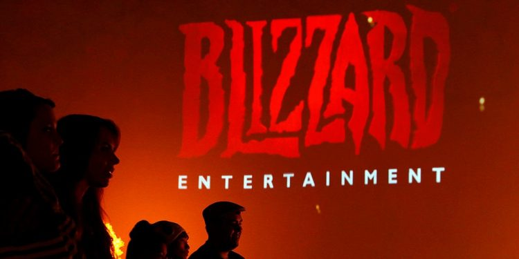 Attendees stand in front of the logo for Blizzard Entertainment Inc., a unit of Activision Blizzard Inc., as they watch a trailer for the company's Diablo III video game during the E3 Electronic Entertainment Expo in Los Angeles, California, U.S., on Wednesday, June 12, 2013. E3, a trade show for computer and video games, draws professionals to experience the future of interactive entertainment as well as to see new technologies and never-before-seen products. Photographer: Patrick T. Fallon/Bloomberg via Getty Images