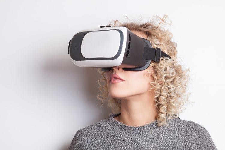 young curly blonde woman in VR glasses on white background